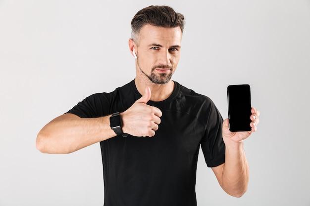 Portret van een gelukkig volwassen sportman in draadloze koptelefoon