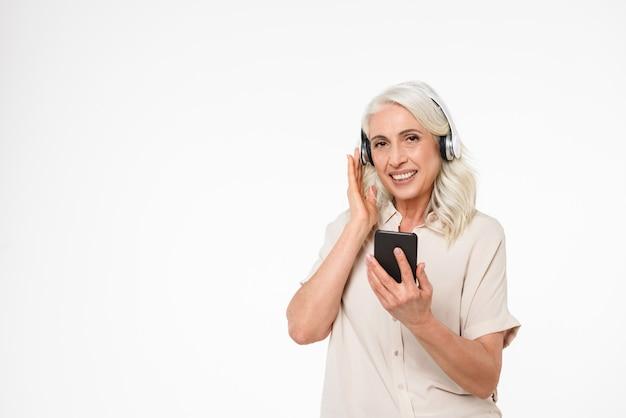 Portret van een gelukkig volwassen vrouw luisteren naar muziek