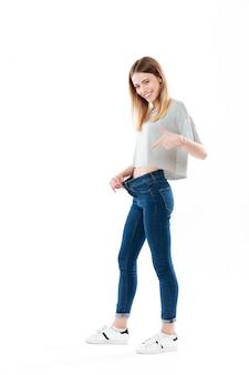 Portret van een gelukkig vreugdevolle jonge vrouw toont haar gewichtsverlies