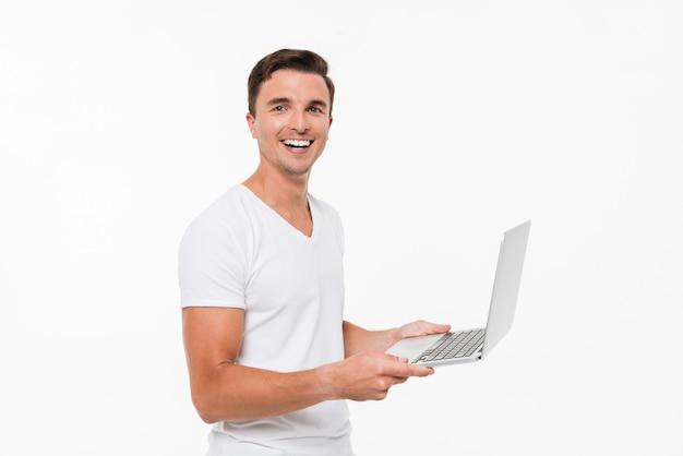 Portret van een gelukkig vreugdevolle man die op laptop werkt