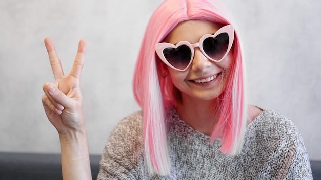 Portret van een gelukkig vrolijk meisje dat vredesgebaar toont. vrouw met hartvormige bril en roze pruik - positief portret