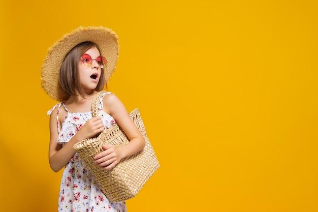 Portret van een gelukkig vrolijk meisje in de strozak van de de zomerhoedzonnebril over gele achtergrond