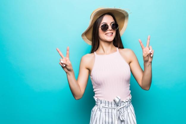 Portret van een gelukkig vrolijk meisje in de zomerhoed die vredesgebaar met twee handen toont die over blauwe muur wordt geïsoleerd.