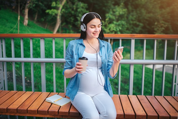Portret van een gelukkig zwart haar en trotse zwangere vrouw in het park. ze zit op een stadsbank. aanstaande moeder luistert naar muziek in het park met een ongeboren kind