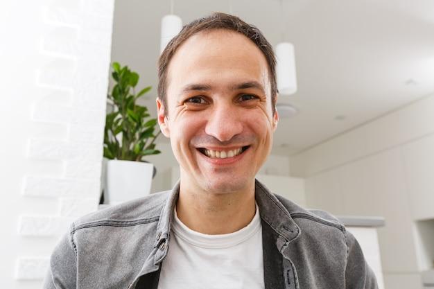 Portret van een gelukkige 30-jarige man in casual kleding die facetime videobellen thuis maakt.