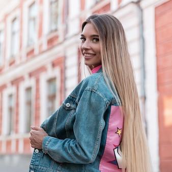 Portret van een gelukkige aantrekkelijke jonge vrouw met een leuke glimlach in modieuze denimkleren