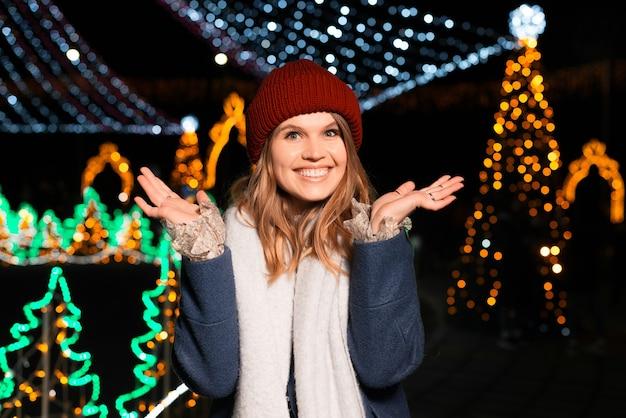 Portret van een gelukkige afgevraagd jonge vrouw 's nachts buiten.