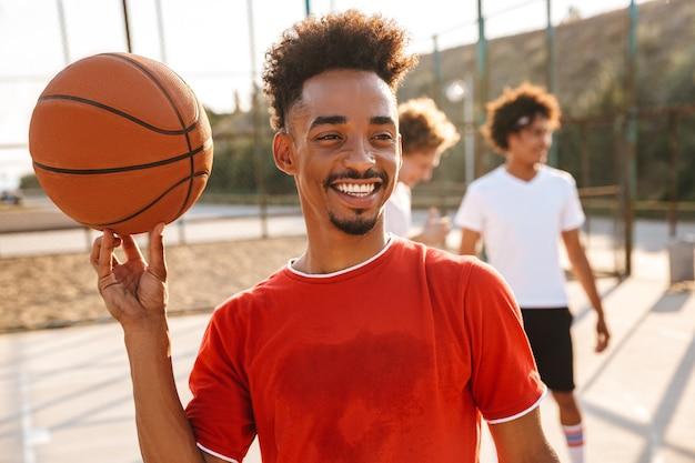 Portret van een gelukkige afrikaanse jongen die bal op zijn vinger draait, terwijl hij met zijn team basketbal speelt op de speelplaats buiten