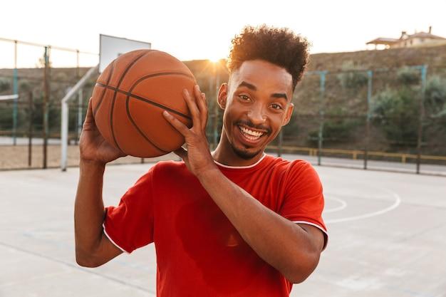 Portret van een gelukkige afrikaanse man met bal, tijdens het spelen van basketbal op de speelplaats buiten