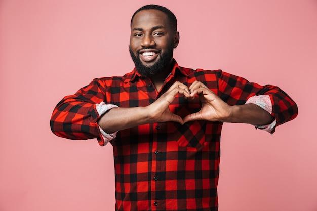 Portret van een gelukkige afrikaanse man met een geruit hemd dat geïsoleerd staat over een roze muur