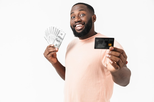 Portret van een gelukkige afrikaanse man met een shirt dat geïsoleerd staat, met geldbankbiljetten en creditcard