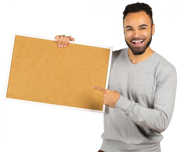Portret van een gelukkige afro amerikaanse mens die lege raad houdt die op een wit wordt geïsoleerd