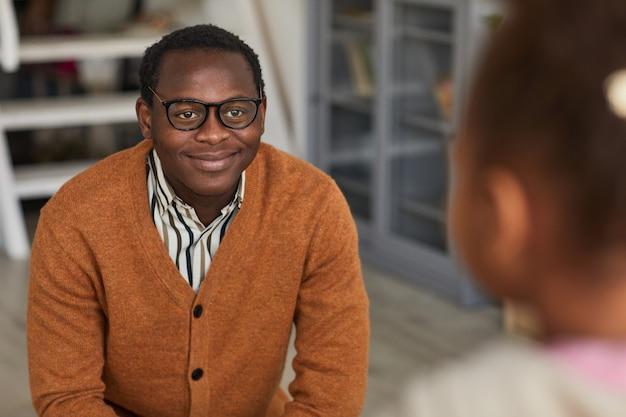 Portret van een gelukkige afro-amerikaanse vader die thuiskomt van zijn werk en zoon ontmoet, kopieer ruimte