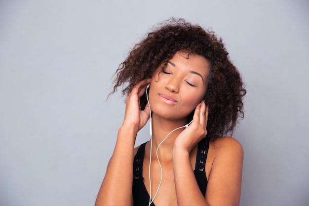 Portret van een gelukkige afro-amerikaanse vrouw die aan muziek in oortelefoons over grijze muur luistert
