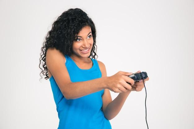 Portret van een gelukkige afro-amerikaanse vrouw die in videogame met joystick speelt die op een witte muur wordt geïsoleerd