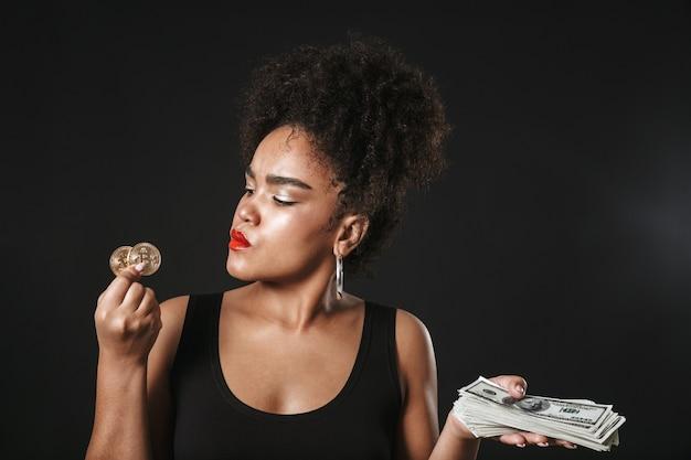 Portret van een gelukkige afro-amerikaanse vrouw die make-up draagt ?? die zich geïsoleerd over zwarte ruimte bevindt