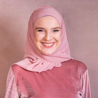 Portret van een gelukkige arabische vrouw tegen gekleurde achtergrond