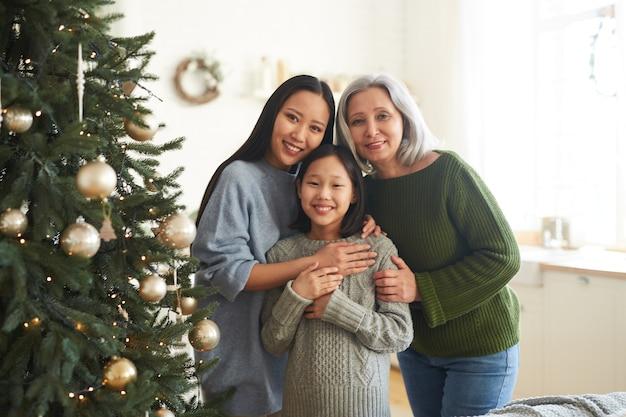Portret van een gelukkige aziatische familie van drie glimlachend staande in de buurt van de versierde kerstboom thuis