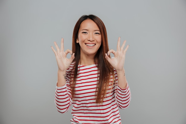 Portret van een gelukkige aziatische vrouw die ok gebaar toont