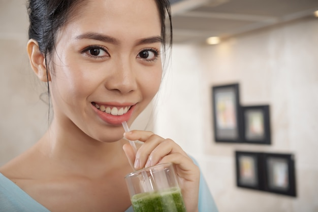 Portret van een gelukkige aziatische vrouw die smoothie drinkt