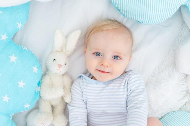 Portret van een gelukkige babyjongen zes maanden oud op een bed, schattige blonde baby