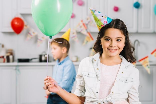 Portret van een gelukkige ballon van de meisjesholding met jongen die op achtergrond lopen