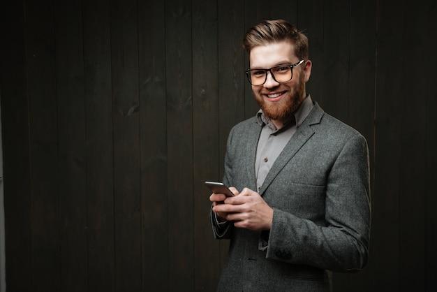 Portret van een gelukkige bebaarde man in casual pak met mobiele telefoon