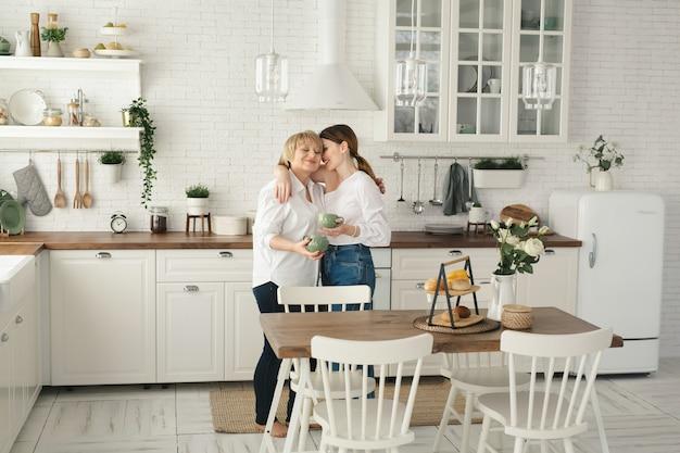 Portret van een gelukkige bejaarde moeder en dochter in de keuken, ze drinken thee en genieten van een gesprek. inschrijving portret van een oude moeder met een volwassen dochter thuis