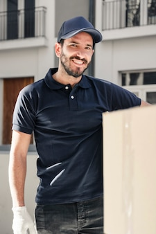 Portret van een gelukkige bezorger met kartonnen doos