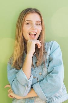 Portret van een gelukkige blonde jonge vrouw tegen mintgroene achtergrond