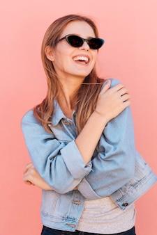 Portret van een gelukkige blonde jonge vrouw tegen roze achtergrond