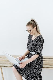 Portret van een gelukkige blonde vrouw in een bril die op laptop werkt