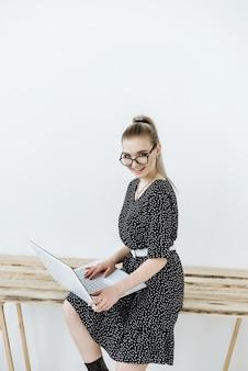 Portret van een gelukkige blonde vrouw met een bril die op laptop werkt