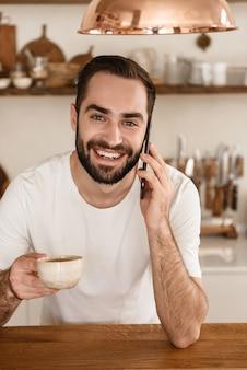 Portret van een gelukkige brunette man die koffie drinkt en smartphone gebruikt terwijl hij thuis ontbijt in een stijlvolle keuken