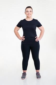 Portret van een gelukkige dikke sportvrouw die geïsoleerd op een witte muur staat