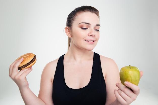 Portret van een gelukkige dikke vrouw die kiest tussen hamburger of appel geïsoleerd op een witte muur