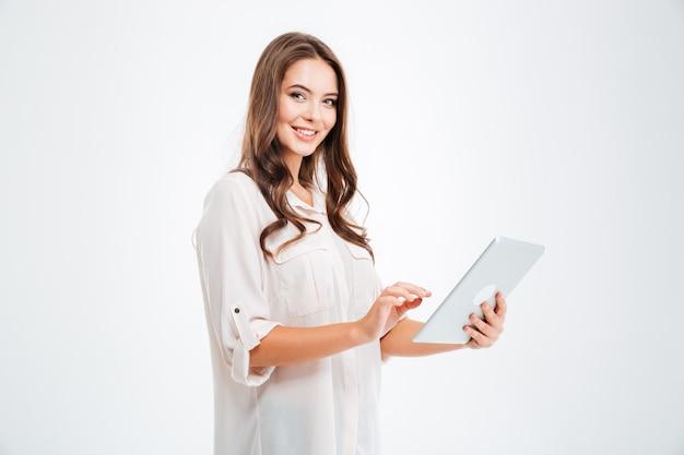 Portret van een gelukkige donkerbruine vrouw die tabletcomputer gebruikt die op een witte muur wordt geïsoleerd