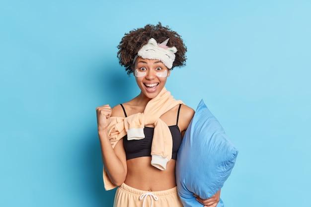 Portret van een gelukkige donkere vrouw steekt vuist op en viert dat er iets thuis blijft op zelfisolatie glimlacht breed