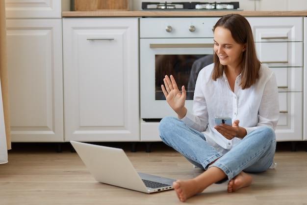 Portret van een gelukkige donkerharige vrouw die een wit overhemd en een spijkerbroek draagt, een smartphone in de hand houdt, naar het scherm van een laptop kijkt en een videogesprek of livestream heeft, met de hand zwaaiend.