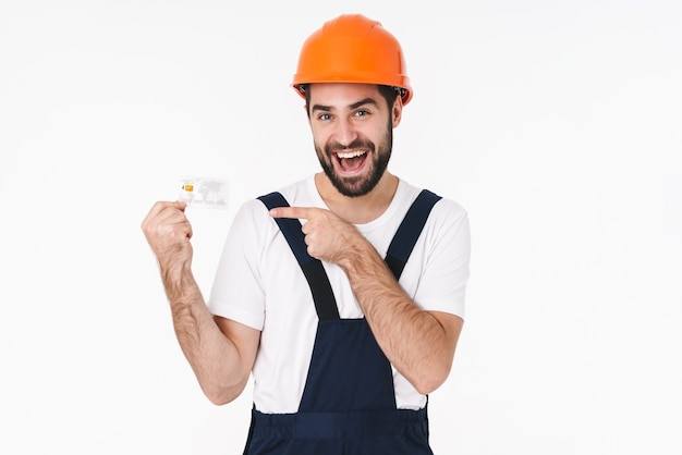Portret van een gelukkige emotionele jonge man bouwer in helm geïsoleerd over een witte muur met creditcard wijzend.