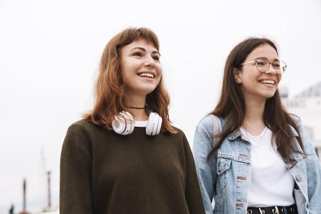 Portret van een gelukkige emotionele jonge mooie vrienden vrouwelijke studenten die buiten lopen en muziek luisteren met een koptelefoon.