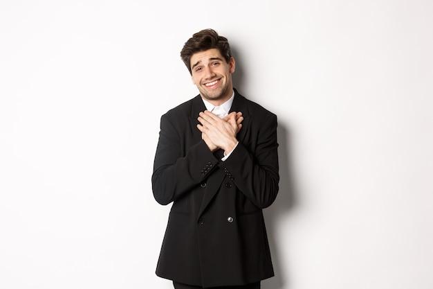 Portret van een gelukkige en blije knappe man in een feestpak, hand in hand op het hart en gevleid zuchtend, bedankt, dankbaar staande op een witte achtergrond.