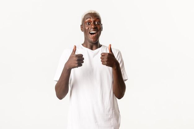 Portret van een gelukkige en opgewonden knappe afro-amerikaanse man, glimlachend verbaasd en duim omhoog in goedkeuring tonen, leuk vinden en iets aanbevelen