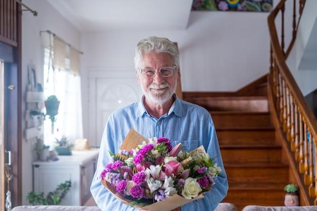 Portret van een gelukkige en schattige oude man die bloemen vasthoudt om aan zijn vrouw of vriendinnen te geven. senior kijken naar de camera thuis met plezier met cadeau of cadeautjes voor valentijnsdag