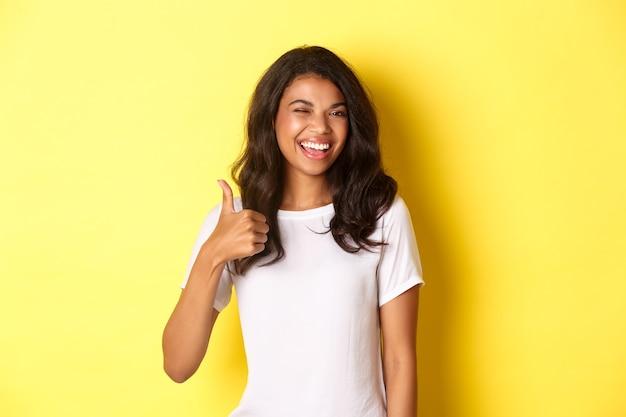 Portret van een gelukkige en tevreden afro-amerikaanse vrouwelijke student, die duimen omhoog laat zien en knipoogt, tevreden glimlacht, iets goeds goedkeurt, je prees, staande over een gele achtergrond.