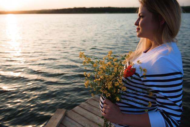 Portret van een gelukkige en trotse zwangere vrouw door de rivier bij zonsondergang.