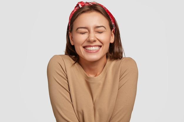 Portret van een gelukkige europese vrouw heeft een brede glimlach, sluit de ogen, voelt opwinding, is in een hoge geest