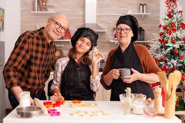 Portret van een gelukkige familie die lacht terwijl ze zelfgemaakt koekjesdeeg vasthoudt