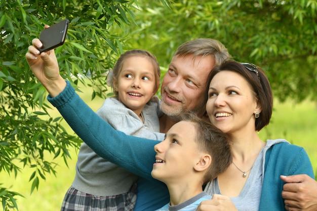 Portret van een gelukkige familie die selfie neemt in het park