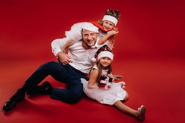 Portret van een gelukkige familie in een kerstmuts op een rode achtergrond. vader en dochters met kerstmis.